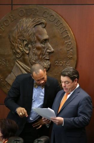 Nevada Senate Minority Leader Aaron Ford, D-Las Vegas, left, and Majority Leader Michael Roberson, R-Henderson, talk on the Senate floor at the Legislative Building in Carson City, Nev., on Friday ...