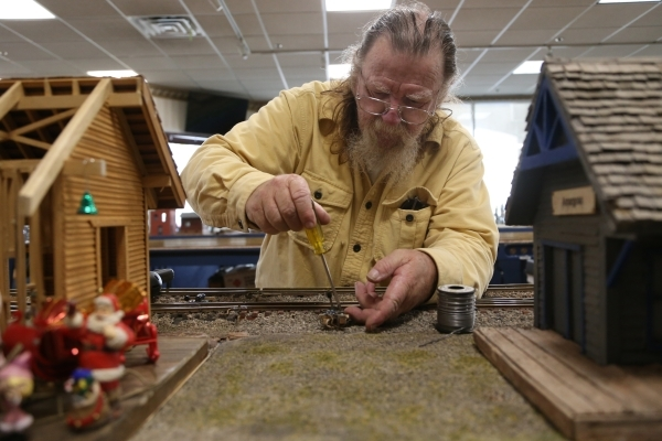 Dale Borst works on the track for the model garden railway display the Las Vegas Railway Society organized at Jim Marsh Kia in northwest Las Vegas Sunday, Dec. 20, 2015. The display will be open t ...