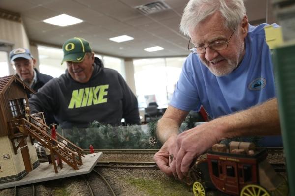 Roy Luehsenhop, Bob Dack, and Richard Poole work on the track for the model garden railway display the Las Vegas Railway Society organized at Jim Marsh Kia in northwest Las Vegas Sunday, Dec. 20,  ...