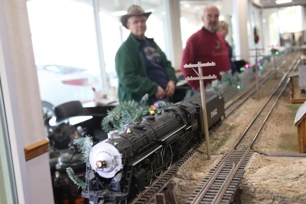 Al Bradshaw and Richard Green watch the first train to test the tracks of the model garden railway display the Las Vegas Railway Society organized at Jim Marsh Kia in northwest Las Vegas Sunday, D ...