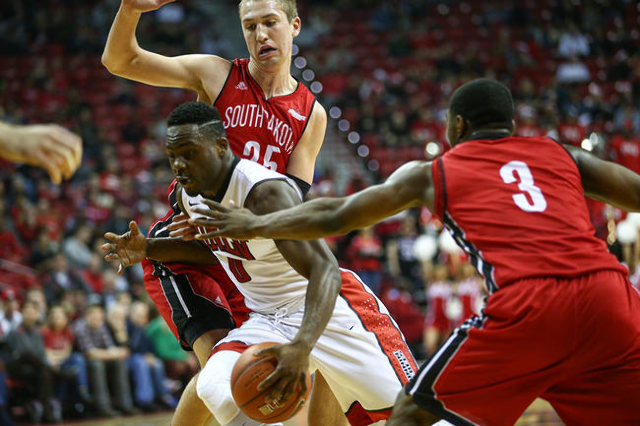 UNLV guard Ike Nwamu (0) drives to the basket past South Dakota's Shy McClelland (3) and Tyler Hagedorn (25) during a basketball game at the Thomas & Mack Center in Las Vegas on Tuesday, ...