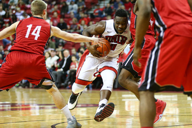 UNLV guard Ike Nwamu (0) drives past South Dakota's Casey Kasperbauer (14) during a basketball game at the Thomas & Mack Center in Las Vegas on Tuesday, Dec. 22, 2015. UNLV won 103-68. C ...