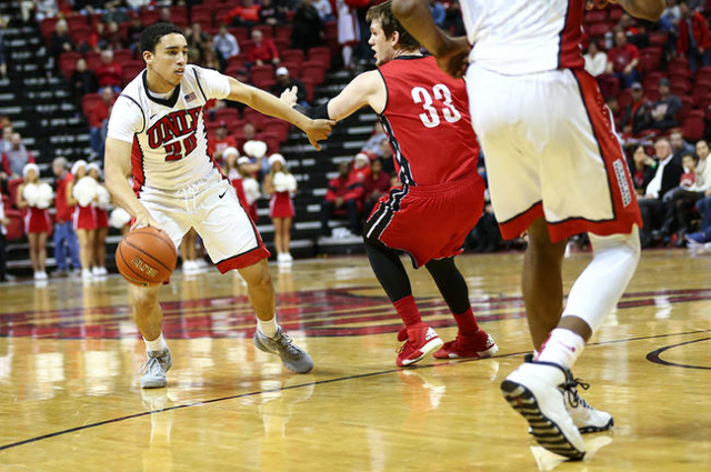 UNLV guard Austin Starr (20) drives past South Dakota's Logan Power (33) during a basketball game at the Thomas & Mack Center in Las Vegas on Tuesday, Dec. 22, 2015. UNLV won 103-68. Cha ...