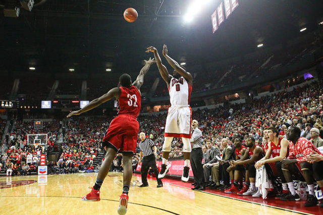 UNLV guard Ike Nwamu (0) shoots to score a three-pointer over South Dakota's D.J. Davis (32) with seconds left on the buzzer at the end of the first half during a basketball game at the Thom ...