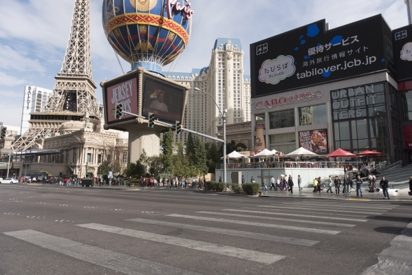 People walk on the sidewalk in front of Paris Las Vegas and Planet Hollywood Resort & Casino in Las Vegas on Monday, Dec. 21, 2015. Jason Ogulnik/Las Vegas Review-Journal.