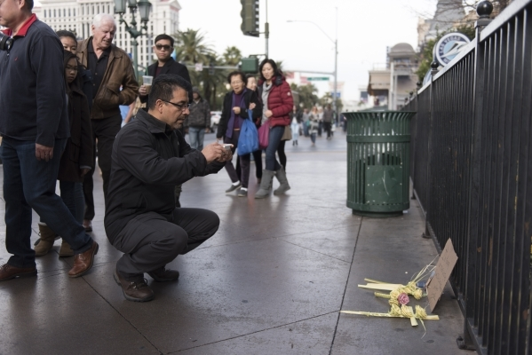 Raul Dorantes takes a photo of the memorial dedicated to the victims of the car crash that took place Sunday night outside of Planet Hollywood Resort & Casino and Paris Las Vegas in Las Vegas  ...