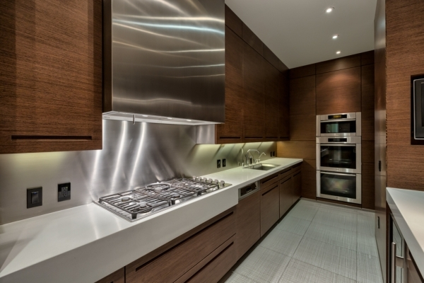 The kitchen has white countertops, a six-burner stove, flat-panel cabinets, a built-in wine fridge and a pull-out pantry, Sub-Zero refrigerator and espresso maker. Its Melange tile floor is matte- ...