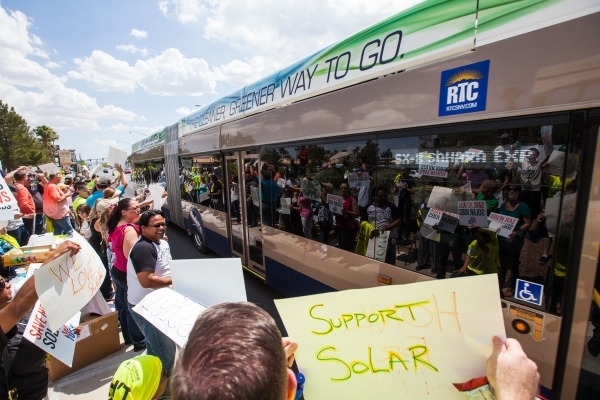 Solar energy supporters are reflected in bus windows while protesting outside of NV Energy at 6226 W. Sahara Ave. on Wednesday, April 22, 2015. Solar energy proponents want Nevada lawmakers to pas ...