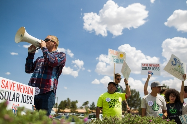 Max Britton, left, speaks as solar energy supporters protest outside of NV Energy at 6226 W. Sahara Ave. on Wednesday, April 22, 2015. Solar energy proponents want Nevada lawmakers to pass a bill  ...