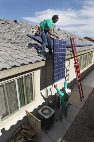 Guillermo Aviles hands a solar panel up to Solar City installation crew leader Greg Kates as they install solar panels on a North Las Vegas home Thursday, Oct. 30, 2014. (Sam Morris/Las Vegas Revi ...