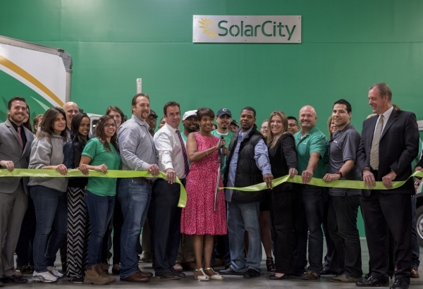 North Las Vegas Councilwoman Pamela Goynes-Brown, center in the red dress, cuts the ribbon during the opening of Solar City's second operation center in North Las Vegas on Tuesday Mar. 10, 2 ...