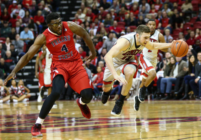UNLV forward Ben Carter (13) trips up after being fouled by Fresno State forward Karachi Edo (4) during a basketball game at the Thomas & Mack Center in Las Vegas on Wednesday, Dec. 30, 2015.  ...