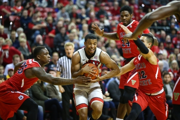 UNLV guard Jerome Seagears (2) drives towards the basket as Fresno State's Marvelle Harris (23), Torren Jones (24) and Cezar Guerrero (12) defend during a basketball game at the Thomas & ...