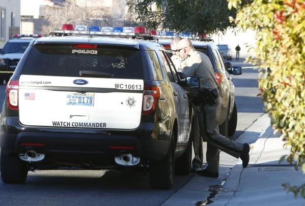 Las Vegas police officers investigate the scene of an officer-involved shooting in the 8300 block of Golden Cypress Avenue, near Desert Inn Road and Durango Drive on Thursday, Dec. 31, 2015. Bizua ...