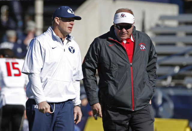 Nov 21, 2015; Provo, UT, USA; Brigham Young Cougars head coach Bronco Mendenhall (left) and Fresno State Bulldogs head coach Tim DeRuyter talk prior to their game at Lavell Edwards Stadium. (Jeff  ...