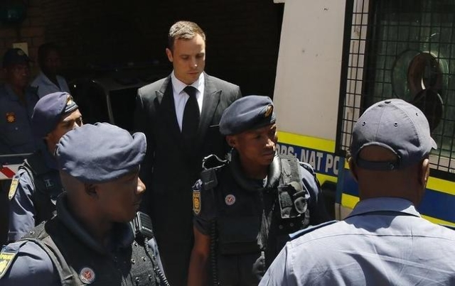 South African Olympic and Paralympic sprinter Oscar Pistorius (C ) is escorted to a police van after his sentencing at the North Gauteng High Court in Pretoria in this October 21, 2014 file photo. ...