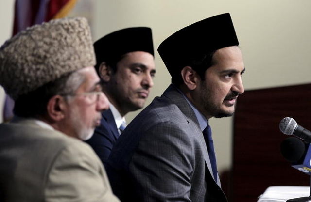 Ashen Khan (R), president of The Ahmadiyya Muslim Community USA, Amjad Mahmood Khan (C), national director of public affairs, and Imam Mohammed Zafarullah, hold a prayer vigil for the victims of W ...