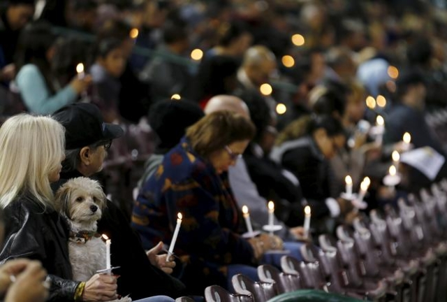 An attendee with a dog reflects on the tragedy of Wednesday's attack during a candlelight vigil in San Bernardino, California December 3, 2015.  REUTERS/Mike Blake