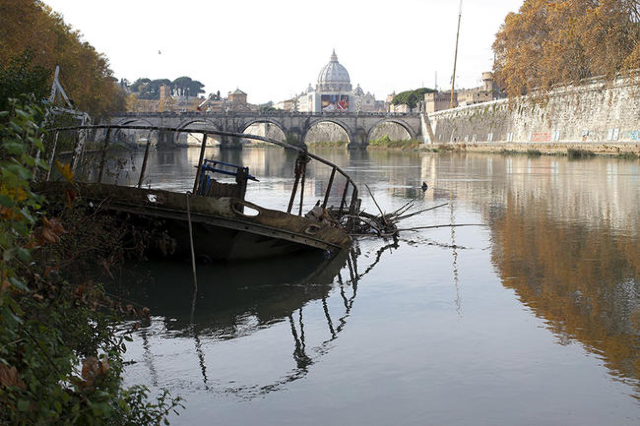 A partially sunk boat is seen on the Tiber river in Rome, Italy, November 30, 2015. Rome is bracing for the arrival of millions of pilgrims for the  Roman Catholic Holy Year which officials had ho ...
