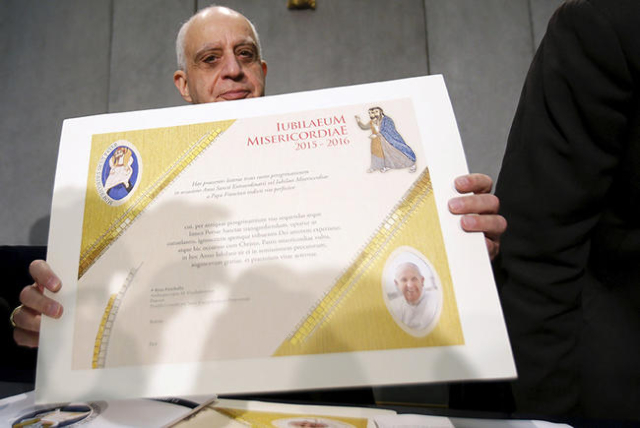 Archbishop Rino Fisichella shows the certificate that will be given to the pilgrims that will arrive at the Vatican by feet during a news conference at the Vatican December 4, 2015. Rome is bracin ...