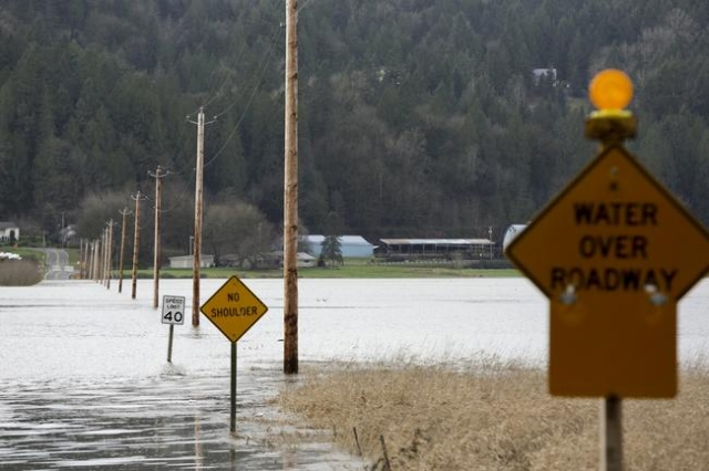 Partially-submerged signs are pictured as flood waters of the Snoqualmie River cover NE 80th Street during a storm in Carnation, Washington December 9, 2015. REUTERS/Jason Redmond