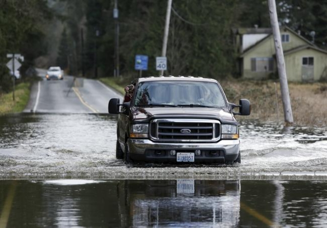 A passenger takes a photo as a truck drives through flood waters of the Snoqualmie River on Ames Lake Carnation Road NE during a storm in Carnation, Washington December 9, 2015. REUTERS/Jason Redmond