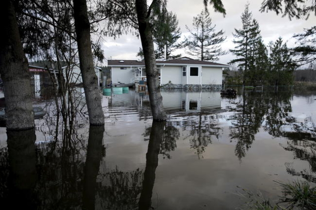 Flood waters of the Snoqualmie River surround a residence off State Route 203 during a storm in Carnation, Washington December 9, 2015. REUTERS/Jason Redmond