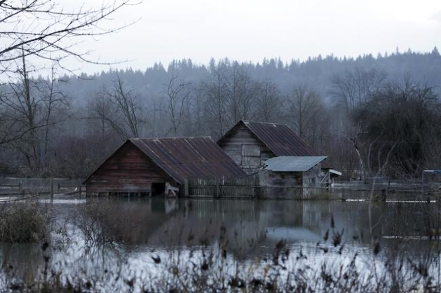 Flood waters of the Snoqualmie River surround a structure off State Route 203 during a storm in Carnation, Washington December 9, 2015. REUTERS/Jason Redmond