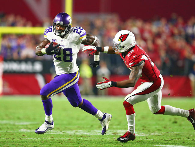 Dec 10, 2015; Glendale, AZ, USA; Minnesota Vikings running back Adrian Peterson (left) runs the ball against Arizona Cardinals cornerback Justin Bethel in the fourth quarter at University of Phoen ...