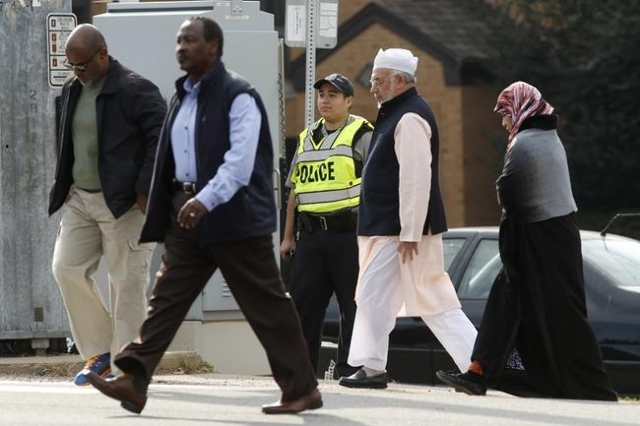 A Fairfax County police officer controls traffic as worshippers make their way to the Dar Al-Hijrah Islamic Center in Falls Church, Virginia  just outside of  Washington December 11, 2015. (Reuter ...