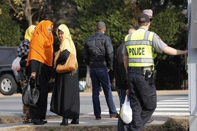 A Fairfax County police officer controls traffic as women make their way to the Dar Al-Hijrah Islamic Center in Falls Church, Virginia  just outside of Washington December 11, 2015. (Reuters/Kevin ...