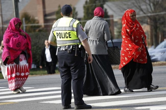 A Fairfax County police officer controls traffic as women make their way to the Dar Al-Hijrah Islamic Center in Falls Church, Virginia  just outside of Washington December 11, 2015.(Reuters/Kevin  ...