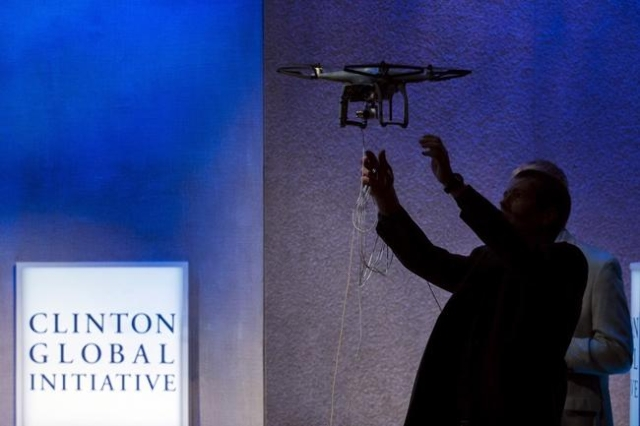 A man reaches out to catch a drone used to monitor rhinos in Africa to protect them from poaching during the Clinton Global Initiative's annual meeting in New York, Sept. 28, 2015. (Lucas Ja ...