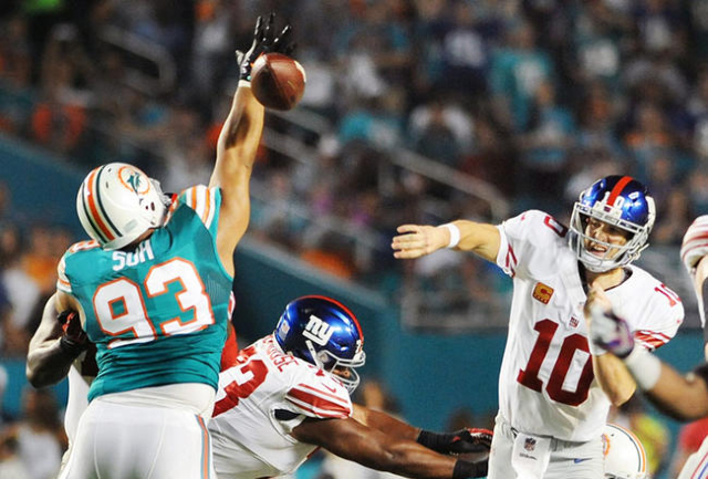 Dec 14, 2015; Miami Gardens, FL, USA; New York Giants quarterback Eli Manning (10) throws as Miami Dolphins defensive tackle Ndamukong Suh (93) defends during the first half at Sun Life Stadium. M ...