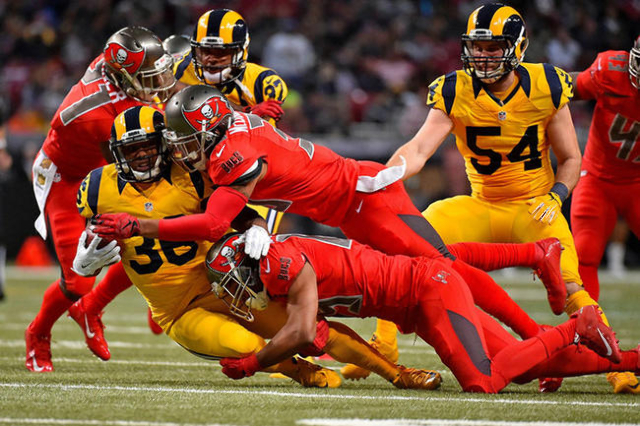 Dec 17, 2015; St. Louis, MO, USA; Tampa Bay Buccaneers wide receiver Russell Shepard (89) and safety Bradley McDougald (30) tackle St. Louis Rams running back Benny Cunningham (36) during the seco ...