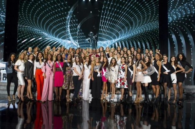 Comedian Steve Harvey poses with the 80 contestants of Miss Universe 2015 in this handout photo provided by The Miss Universe Organization prior to rehearsal at the Planet Hollywood Resort & C ...