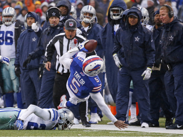 Dec 27, 2015; Orchard Park, NY, USA; Buffalo Bills quarterback Tyrod Taylor (5) runs for a first down as Dallas Cowboys defensive back Deji Olatoye (29) defends during the second half at Ralph Wil ...