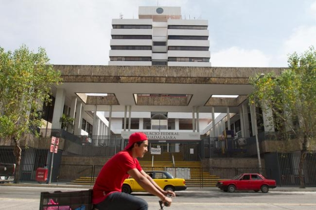 A cyclist pedals past the Jalisco state immigration office, where Ethan Couch and his mother Tonya were in custody and waiting for deportation, in Guadalajara, Mexico, Dec. 30, 2015.  (Javier Hoyo ...