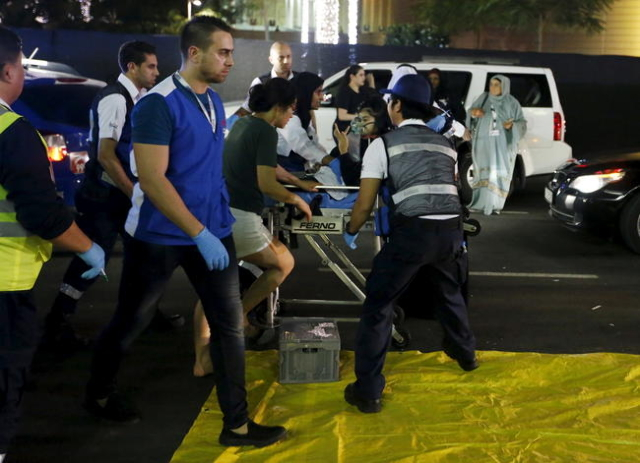 Medics evacuate a wounded person outside the Address Downtown Dubai hotel and residential block after a fire engulfed the skyscraper in downtown Dubai in the United Arab Emirates December 31, 2015 ...