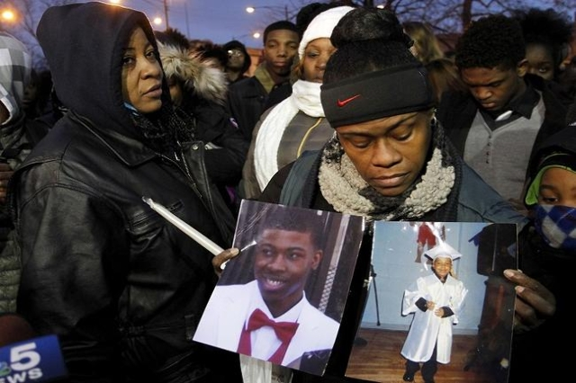 Janet Cooksey (L), birthmother of Quintonio LeGrier, walks away from an interview while a friend holds pictures of LeGrier shortly before a candlelight vigil in honor of Bettie Jones, a mother of  ...