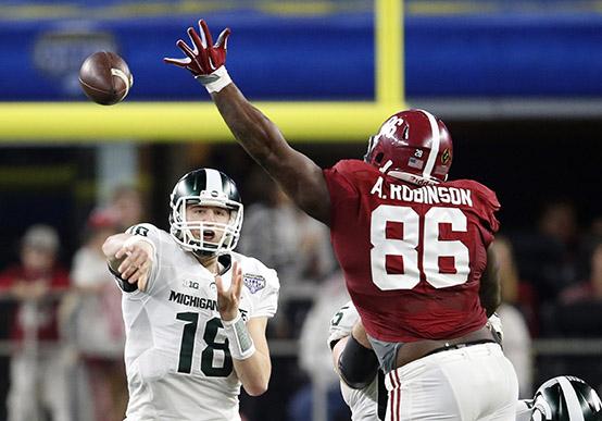 Dec 31, 2015; Arlington, TX, USA; Michigan State Spartans quarterback Connor Cook (18) throws a pass past Alabama Crimson Tide defensive lineman A'Shawn Robinson (86) in the second quarter i ...