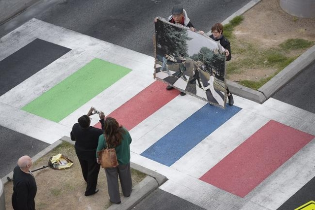 """Beatle fans have their photo taken holding a tapestry depicting the cover of the Beatles """"Abbey Road"""" album at the """"Abbey Road Crossing"""" on Fremont Street on the 35th anniversa ..."""