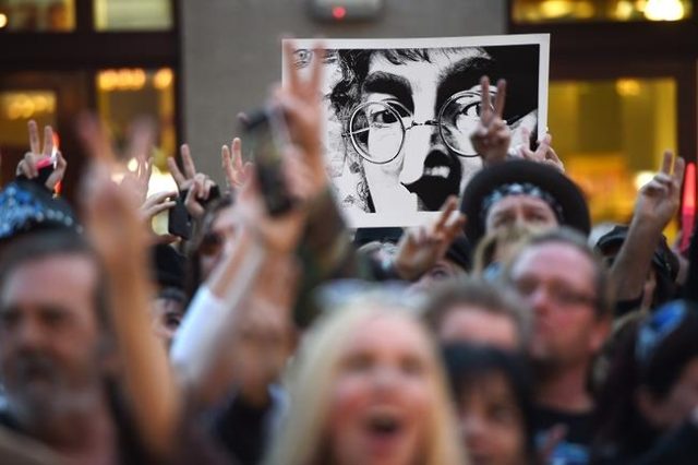 """A Beatles fan holds up a poster of John Lennon while a gathering sings """"All You Need is Love"""" at the """"Abbey Road Crossing"""" on Fremont Street on the 35th anniversary of John Len ..."""