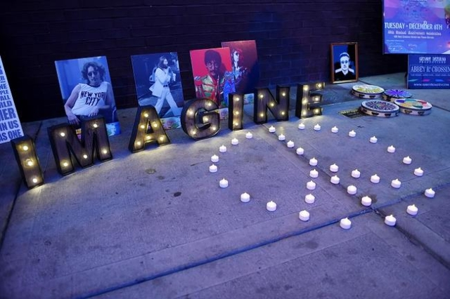 """Lights and photos of John Lennon are arraigned on the sidewalk at the """"Abbey Road Crossing"""" on Fremont Street on the 35th anniversary of John Lennon's murder Tuesday,  Dec. 8, 2015 ..."""
