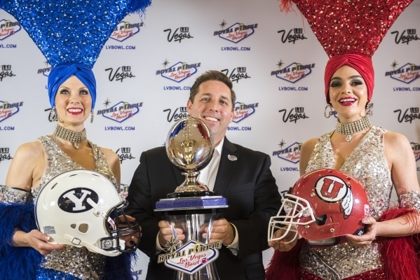 Las Vegas Bowl Executive Director John Saccenti, center, poses with showgirls Jennifer Autry, left, and Porsha Revesz at a press conference in Las Vegas on Sunday, Dec. 6, 2015. BYU will take on N ...