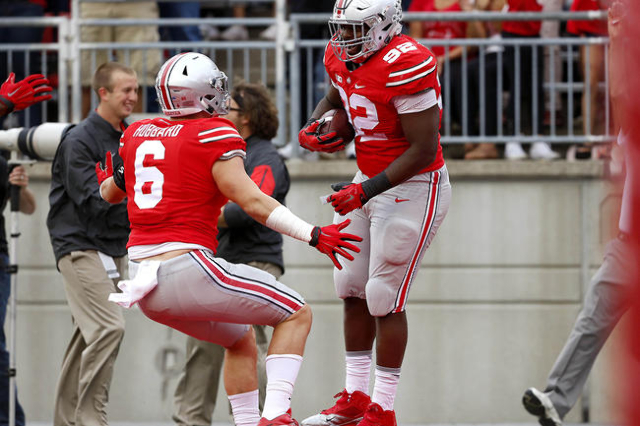 Sep 26, 2015; Columbus, OH, USA; Ohio State Buckeyes defensive lineman Adolphus Washington (92) celebrates his interception return for a touchdown with teammate Sam Hubbard (6) during the second q ...