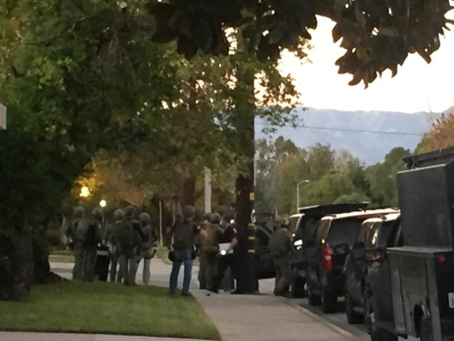 SWAT and other law enforcement swarm the area looking for suspects from the mass shooting at the Inland Resource Center in San Bernardino.
