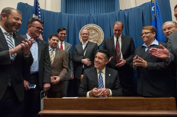 Gov. Brian Sandoval smiles after signing all the special session bills at the Capitol Building in Carson City, Nev., on Saturday, Dec. 19, 2015. Sandoval convened a special Legislative session to  ...