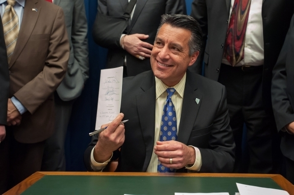 Gov. Brian Sandoval signs Assembly Bill 1 at the Capitol Building in Carson City, Nev., on Saturday, Dec. 19, 2015. Sandoval convened a special Legislative session to vet an economic development d ...