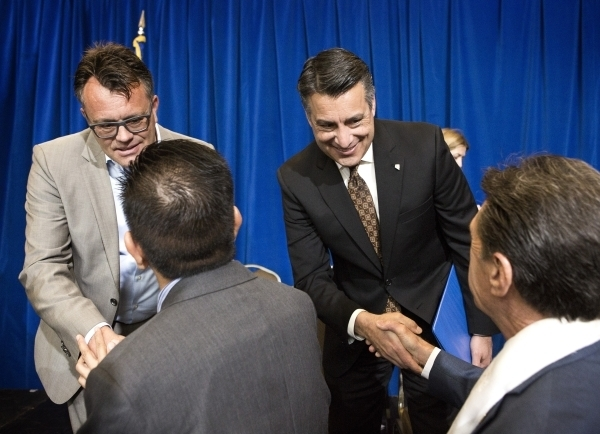 Dag Reckhorn, left, global vice president for Faraday Future, and Gov. Brian Sandoval are congratulated by guests during the company's announcement at the Sawyer Building onThursday, Dec. 10, 20 ...